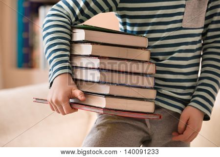 Little boy in a striped shirt holding a pile of books. Education and knowledge concept. Reading children. Back to school. Happy reading. Schoolboy at the library.