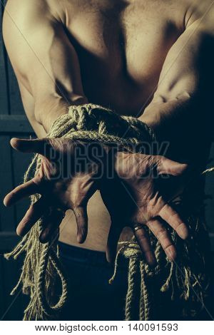 Sport. Young man with muscular body tied with rope