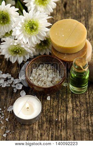 spring flower, pile of salt ,massage oil ,soap, on old wood