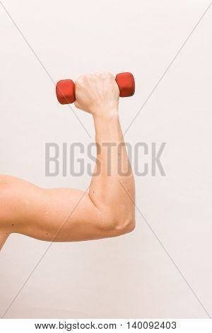 Close-up of strong man's arm holding small red dumbbell on white background. Fitness and health concept. Hand bent at the elbow holding a dumbbell. Muscular arm with dumbbell close up