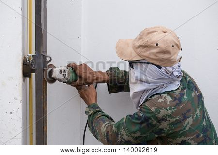 Worker Using Grinder To Grinding Metal