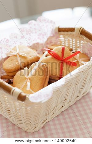 White basket with homemade crispy cookies decorated with thin ribbons. Cookies on the table. Preparations for holiday season. Baking at home.