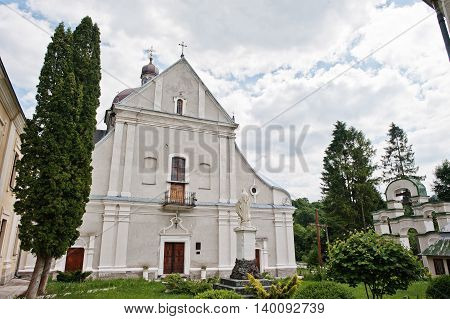 White Stone Catholic Church With A Bell Tower And Monument Of Holy Mary