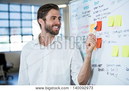 Businessman smiling while pointing on sticky note stuck to whiteboard in meeting room