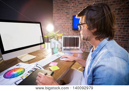 Male graphic designer using computer in creative office