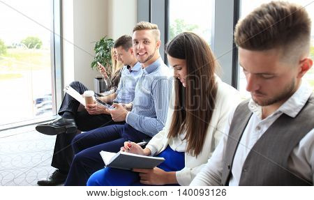 Smiling businessman looking at camera at seminar with her colleagues near by
