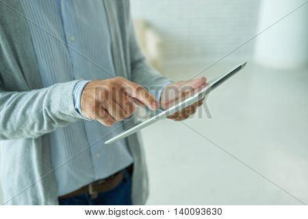 Hands of person using digital tablet in office