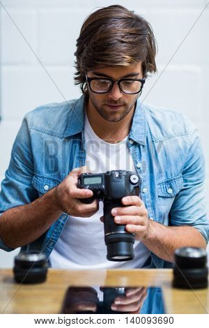 Focused young man holding camera in creative office