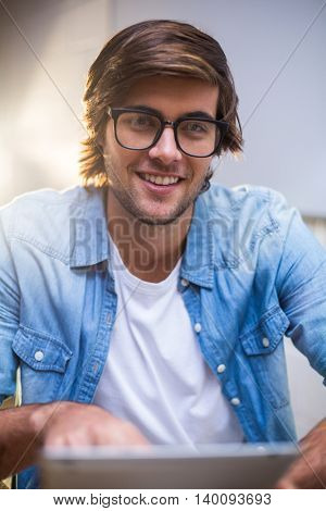 Portrait of happy young man using in creative office