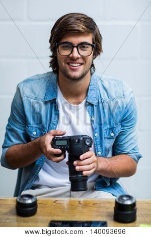 Portrait of happy young man holding camera in creative office