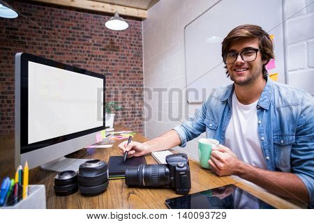 Portrait of smiling male graphic designer working in creative office