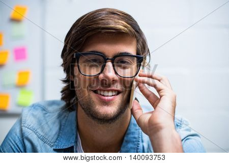 Portrait of smiling young man talking on phone in creative office