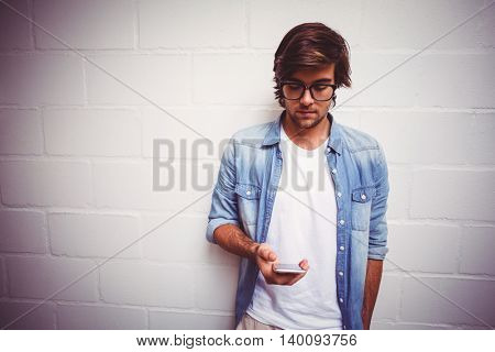 Young man using mobile phone while standing against wall