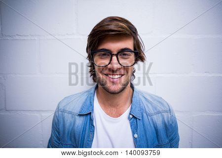 Portrait of smiling young man standing against wall