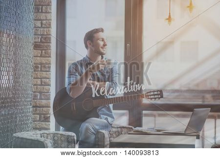 Just relax. Inspirational typographic poster for relaxation with image of smiling man drinking coffee and holding guitar in a background