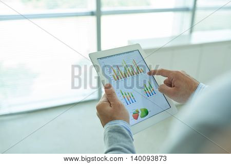 Hands of business executive analyzing chart of digital tablet
