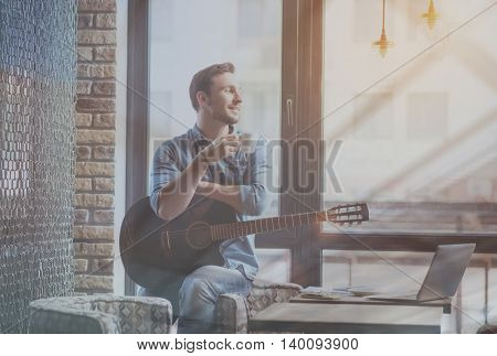 Just me. Happy and optimistic young man sitting on an armchair near window, drinking coffee and holding guitar