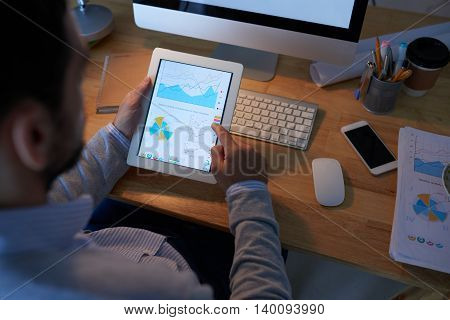 Businessman analyzing chart of tablet, view from the shoulder