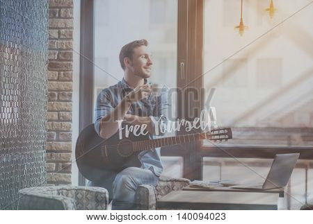 Positive feelings. Inspirational motivational typographic text about free yourself with image of smiling man drinking coffee and holding guitar in a background