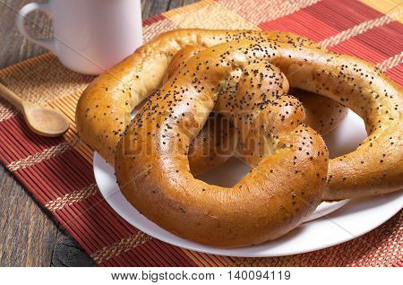 Soft pretzels with coffee cup for breakfast on bamboo napkin