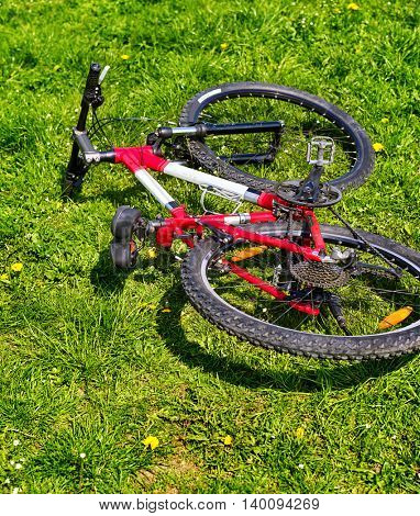 City bicycle lying on green grass . No people. Bicycle concept