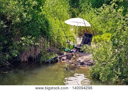 Fishing spot and gear in green landscape chair and fishing rod by tje river