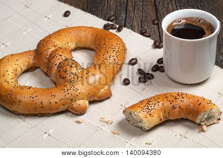 Cup of hot coffee with tasty pretzels for breakfast on napkin located on the table