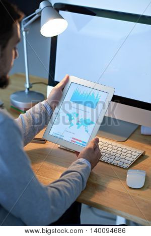 Digital tablet with financial chart in hands of business person