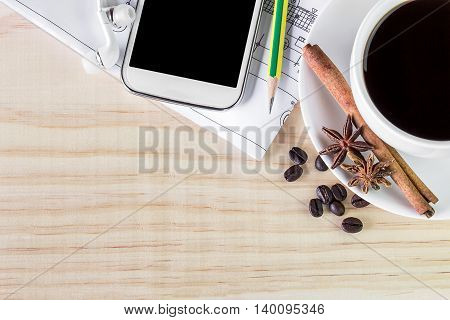 Cup of coffee and smart phone with coffee beans on wooden table background. top view with copy space. Business concept