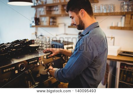 Young man taking coffee from espresso machine at office cafeteria
