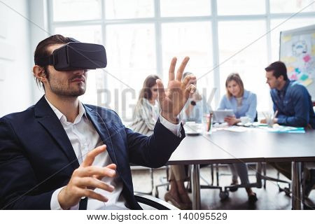 Businessman using virtual reality simulator against colleagues in meeting room at office