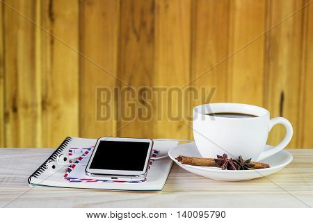 Cup of coffee and smart phone on wooden table background. top view with copy space. Business concept