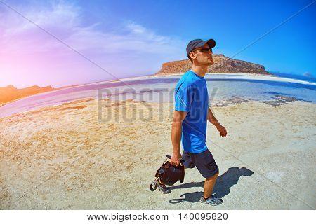 man walking on the empty sunny beach, Crete, Greece