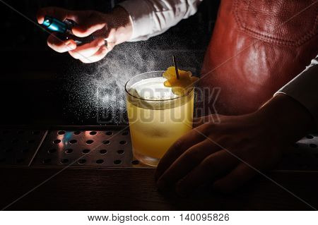 Expert barman is spraying on cocktail no face