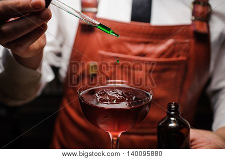 Expert barman is making cocktail and finishing up by dropping green bitter