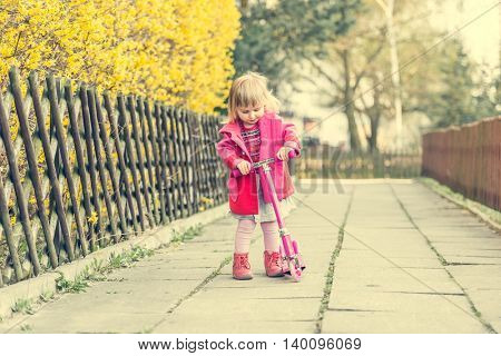 year-old girl riding her scooter on the street