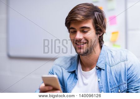 Smiling young man using mobile phone in creative offive