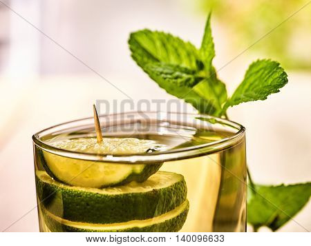 Alcohol drink. On wooden boards top of glass with alcohol green transparent drink. Drink two hundred sixty-eight cocktail green tea decorated with lime and mint leaf. Country life. Light background.