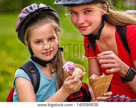 Two bikes bicyclist girl. Girls wearing bicycle helmet with rucksack rides bicycle. Girls children are bicycling in summer park. Happy bicycle girls biking eating ice cream cone .