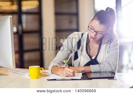 Focused young woman writing on paper in office
