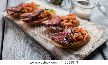 Meat on sliced baguette. Small sandwiches on board. Tasty meal at italian cafe. Proven recipe of bruschetta.
