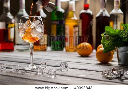 Jigger pours liquid in wineglass. Oranges and cubes of ice. Recipe of refreshing beverage. Drink and enjoy.