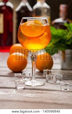 Wineglass with orange beverage. Ice cubes beside oranges. Delicious aperol spritz cocktail. Tasty drink with dry wine.