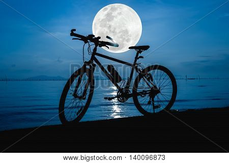 Silhouette Of Bicycle On The Beach Against Beautiful Full Moon In The Sea. Outdoors.