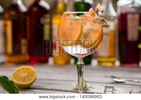 Slices of lemon in beverage. Decorated glass with cocktail. Take a sip and relax. Standard recipe of tom collins.