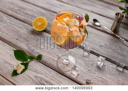 Beverage with lemon in glass. Wineglass on wooden surface. How to prepare tom collins. Best recipe of alcoholic cocktail.
