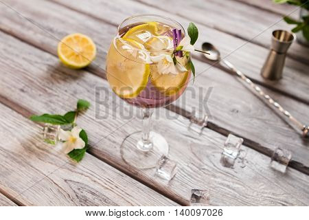Lemon slices inside a drink. Small white flowers and ice. Tom collins with sour juice. Cold alcoholic beverage.