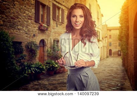beautiful woman in summer day walking and running joyful and cheerful smiling in Tuscany, Italy.