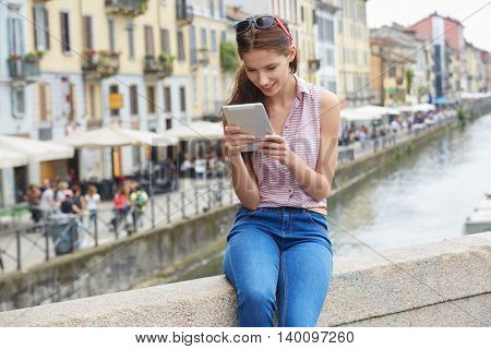 Beautiful woman sitting outdoors and using a tablet watching media content in a sunny windy day in a port of the coast