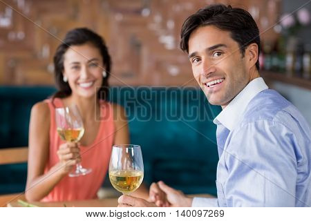 Portrait of young couple having champagne in restaurant